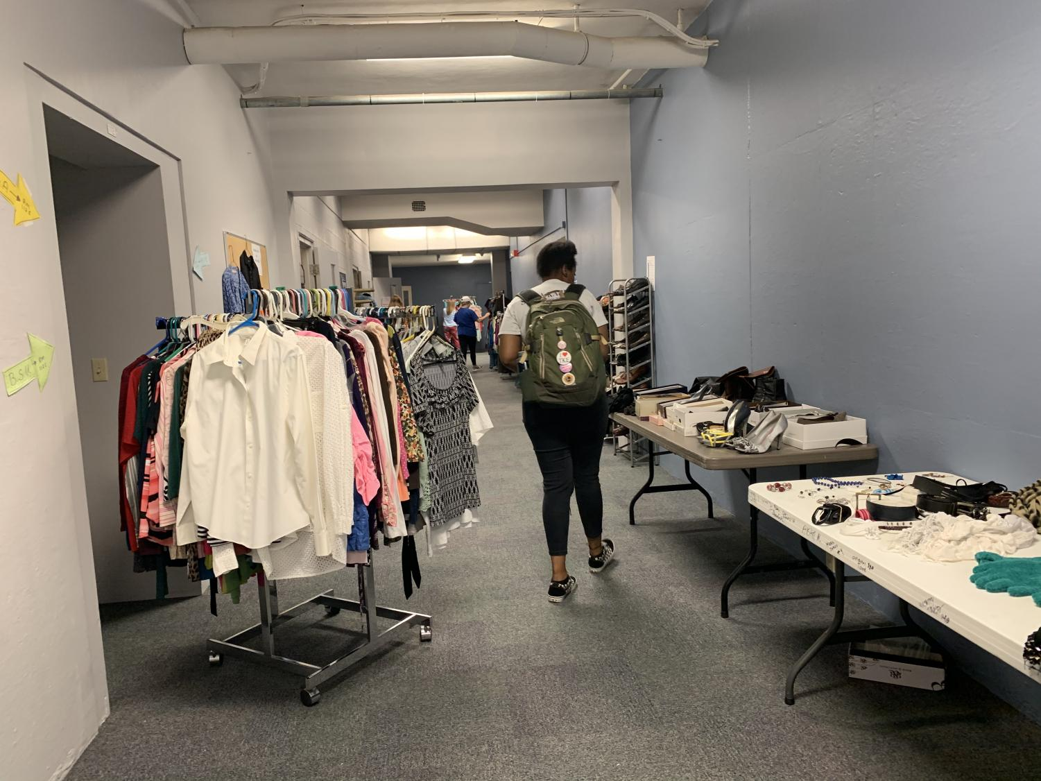 A student walking through the tables of accessories and racks of clothes.