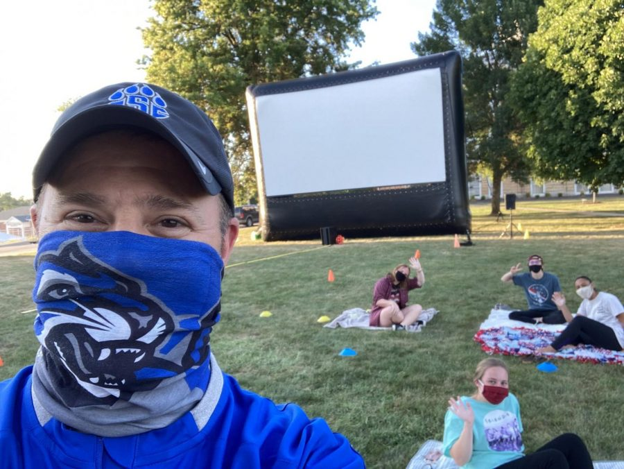President Palmer socially distancing taking a selfie at outdoor movie event with students.